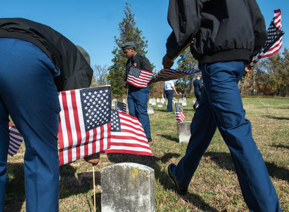 Members of the Anacostia High School Junior ROTC places flags on graves of soldiers during the Veterans Remembrance Ceremony at Saint Elizabeths Hospital East Campus. Photo by Susana Raab/Anacostia Community Museum/Smithsonian Institution