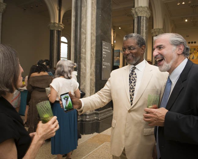 June 12, 2015 -ACM Board Chair Larry Frazier shows off his 70s themed outfit on his phone to Allyn Kurin with Undersecretary Richard Kurin at the Anacostia Community Museum annual soiree held at the Smithsonian Castle on the Mall. Photo by Susana Raab/Anacostia Community Museum/Smithsonian Institution