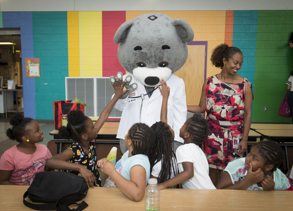 June 29, 2015 - Children members of the Anacostia Community Museum Academy interact with the mascot of United Healthcare during an event at Savoy Eleementary School in SE Washington for a joint event announcing the launch of a health and wellness partnership between the Childrens' National Health System, Monumental Sports, and the Smithsonian Anacostia Museum. Photo by Susana Raab/Anacostia Community Museum/Smithsonian Institution