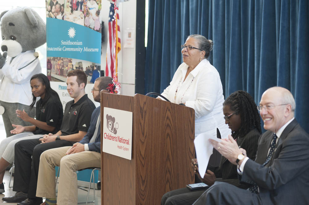 June 29, 2015 - Anacostia Community Museum Director Camille Akeju makes opening remarks at the Savoy Elementary School in SE Washington for a joint event announcint the launch of a health and wellness partnership between the Childrens' National Health System, Monumental Sports, and the Smithsonian Anacostia Museum. Photo by Susana Raab/Anacostia Community Museum/Smithsonian Institution