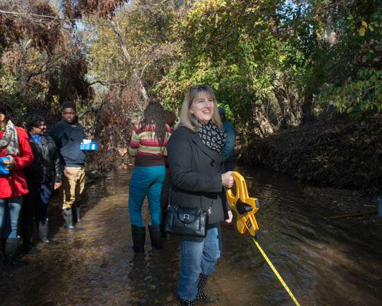 October 31, 2015- Smithsonian Director Michelle Delaney helps anchor a point of measurement during a visit to a tributary of the Anacostia Watershed near Kennilworth Park to watch the Anacostia Community Museum's Citizen Scientist Program test water levels.  The program received support from State Farm. Susana Raab/Anacostia Community Museum/Smithsonian Institution