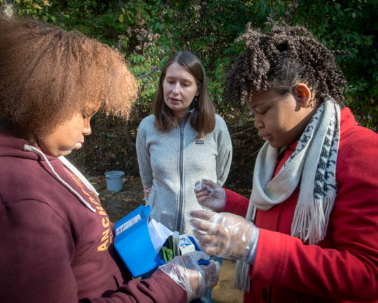 October 31, 2015- Howard University biology professor Jenelle Burke watches over two students, Takia Holstein, left, and M'Kya Denny, right, during an outing to a tributary of the Anacostia Watershed near Kennilworth Park in support of the Anacostia Community Museum's Citizen Scientist Program which received support from State Farm. Susana Raab/Anacostia Community Museum/Smithsonian Institution