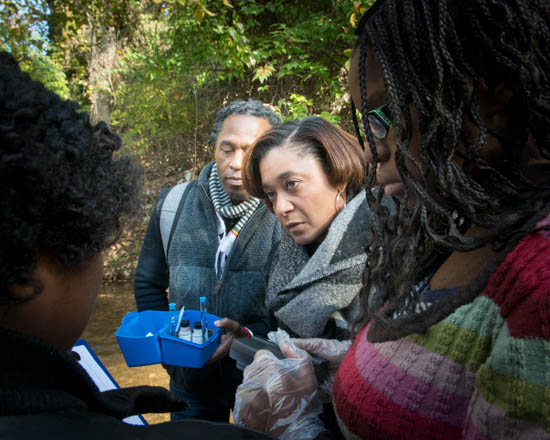October 31, 2015- Graduated student Cristal Sandoval assists new student Iyona Whitehead while Howard University Chemistry Professor Vernon Morris and State Farm Representative Angela Rosser watch the test they students are conducting.  The group were on an outing to a tributary of the Anacostia Watershed near Kennilworth Park in support of the Anacostia Community Museum's Citizen Scientist Program which received support from State Farm. Susana Raab/Anacostia Community Museum/Smithsonian Institution