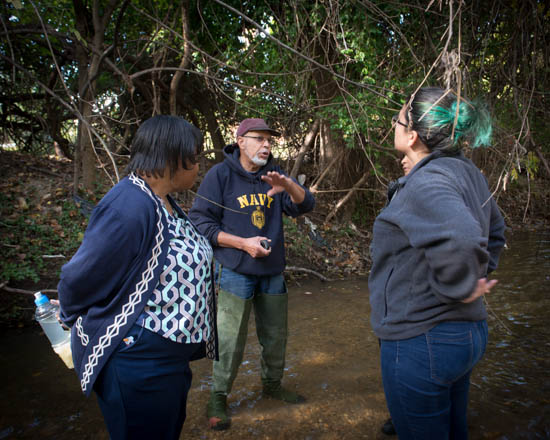 October 31, 2015- Citizen Scientists Program manager Tony Thomas chats with Rebecca Bankhead of the Univeristy of DC, and Cassandra Carcamo of State Farm, during an outing to a tributary of the Anacostia Watershed near Kennilworth Park in support of the Anacostia Community Museum's Citizen Scientist Program which received support from State Farm. Susana Raab/Anacostia Community Museum/Smithsonian Institution