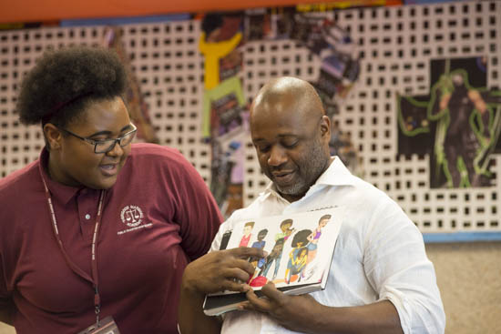 September 14, 2016 - A student from Thurgood Marshall Academy in southeast Washington shows her artwork to artist Theaster Gates. He and his associates the Black Monks of Mississippi performed at the Hirshhorn Museum in advance of Gates' presentation at the museum later that night in honor of the opening of the new Museum of African American History and Culture. Susana Raab/Anacostia Community Museum/Smithsonian Institution
